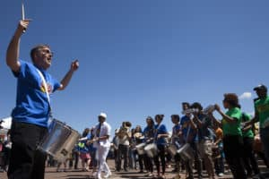 Associate Professor of Music directs Samba Ensemble outside.