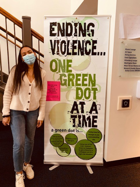 student standing near large green dot sign which reads, ending violence one green dot at a time