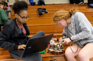 Trinity students make last-minute adjustments to their robot.