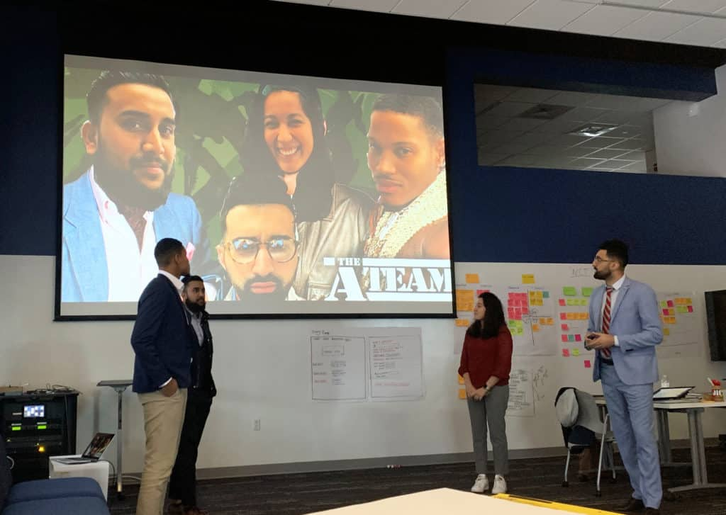 Trinity alumni Tim Flynn '19 (front left) and Francesca L. Velarde '19 (second from right) give a presentation during their Infosys training at Trinity's Liberal Arts Action Lab on Constitution Plaza.
