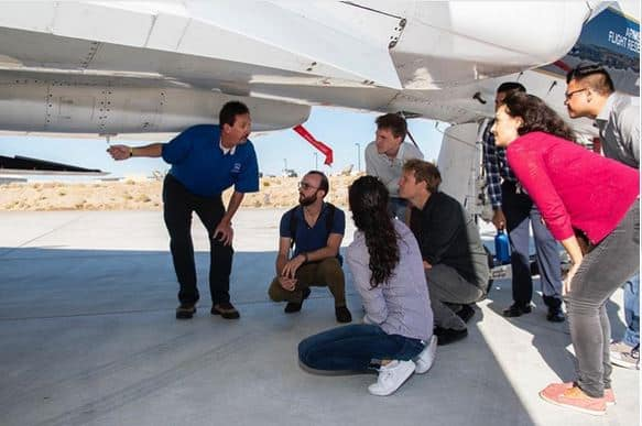Interns look under an F-15 with a NASA engineer.
