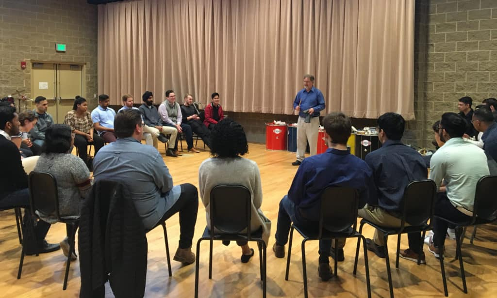 Trinity Associate Professor of Music Eric Galm instructs an Infosys training group on active listening in Trinity's Gruss Music Center.