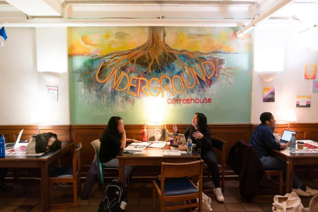 Two students work and socialize at a table with a large painting of the Underground Coffeehouse logo on the wall above them.