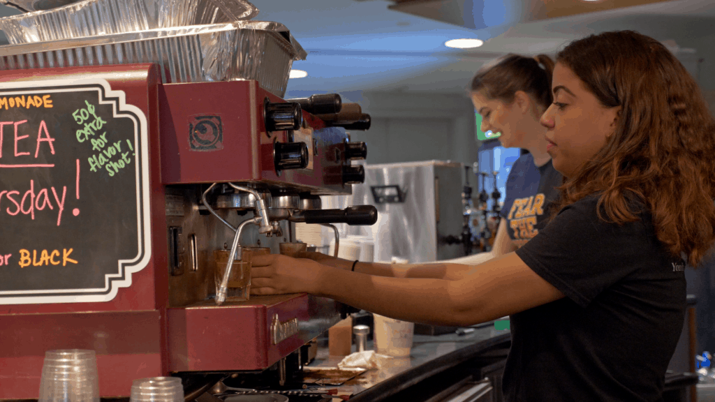 Two students prepare coffee drinks at an espresso machine