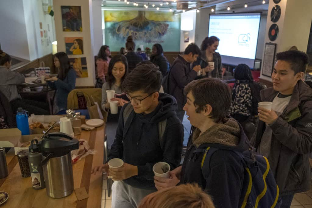 Many students socialize in the open space of the coffeehouse while drinking coffee.