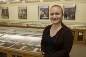 """Abigail Waldron M'20 stands near the """"Pulp Art of Science Fiction's Golden Age"""" exhibit she curated."""