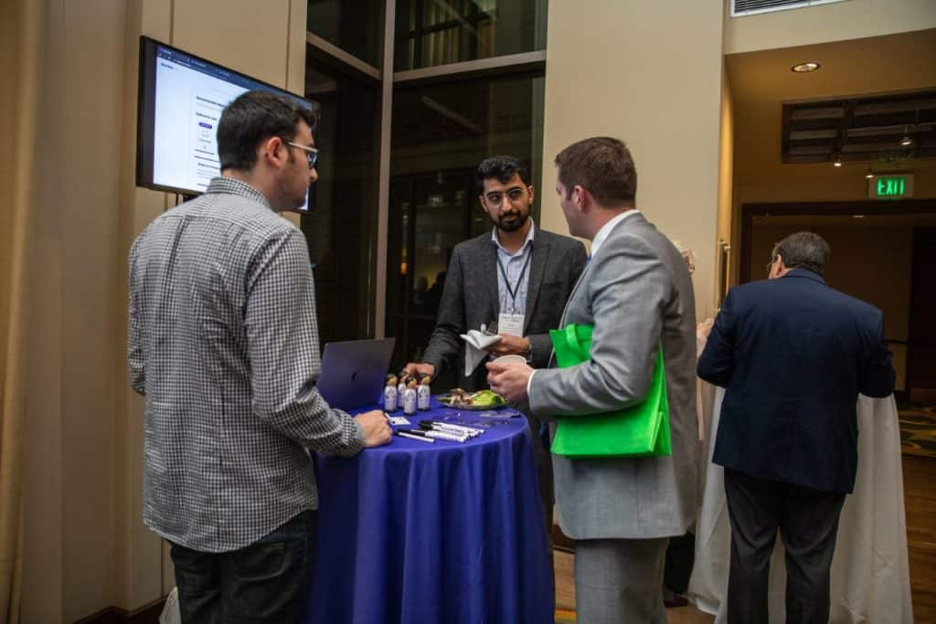 Clearstep CEO Adeel Malike (center) and CMO/Chief of Design Peter Garber (left), both co-founders, networking with a Demo Day attendee after pitches.